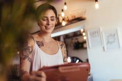 Kobieta przedsiębiorca przy fakturowaniem odpierającym jej restauracja zdjęcia stock