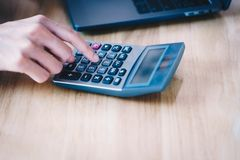 Kobieta przedsiębiorca używa kalkulatora kalkulować pieniężnego e obrazy stock
