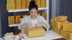 Kobieta przedsiębiorca wiąże arkany i pakujący produkty w pakuneczka pudełku, przygotowywa dla dostawy klienci w ministerstwo spr zdjęcie wideo