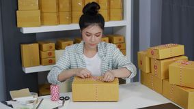 Kobieta przedsiębiorca wiąże arkany i pakujący produkty w pakuneczka pudełku, przygotowywa dla dostawy klienci w ministerstwo spr zbiory wideo