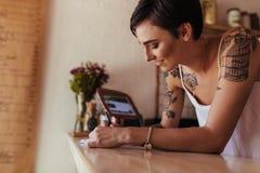 Kobieta przedsiębiorcy pozycja przy fakturowaniem odpierającym jej kawiarnia zdjęcia royalty free