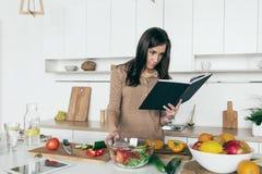 Kobieta przepisu przyglądającej jarzynowej sałatkowej książki kucharskiej Prosty zdrowy foo zdjęcia royalty free