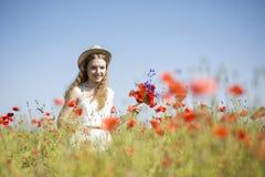 Kobieta przy bielu suknia znajdującym pięknym kwiatem Fotografia Stock