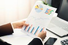 Kobieta przy biurem analizuje biznesowego pieniężnego wykres donosi Obrazy Stock