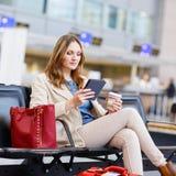 Kobieta przy lotniskiem międzynarodowym czytelniczy ebook i pić coffe, Obrazy Royalty Free
