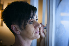 Kobieta przy okno smutnym Zdjęcia Stock