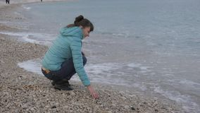 Kobieta przy osamotnioną zimno plażą Atrakcyjna caucasian kobieta bawić się z kamieniami blisko wody na plaży zdjęcie wideo
