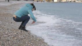 Kobieta przy osamotnioną zimno plażą Kaukaska kobieta odbija się z nadchodzącej fali bawić się z kamieniami blisko wody na zbiory wideo