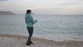 Kobieta przy osamotnioną zimno plażą Kaukaska kobieta rzuca kamienie w spokojnego morze zdjęcie wideo