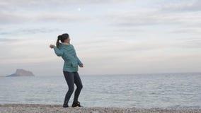 Kobieta przy osamotnioną zimno plażą Kaukaska kobieta rzuca kamienie w spokojnego morze na góry i księżyc w pełni tle zdjęcie wideo