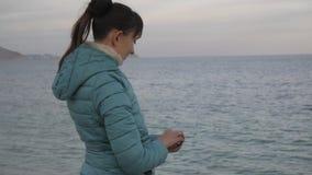 Kobieta przy osamotnioną zimno plażą Midshot caucasian kobiety miotania kamienie w spokojnego morze zdjęcie wideo