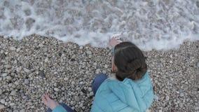 Kobieta przy osamotnioną zimno plażą Przegląda frome nad atrakcyjna caucasian kobieta bawić się z wodą morską na plaży zbiory
