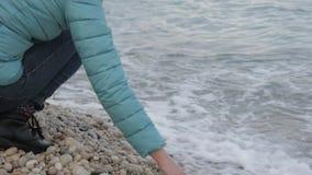 Kobieta przy osamotnioną zimno plażą W górę atrakcyjnej caucasian kobiety bawić się z kamieniami blisko wody na plaży zbiory wideo