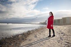 Kobieta przy plażą z czerwonym żakietem zdjęcie stock