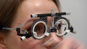 Kobieta przy przyjęciem oftalmologa oka egzamin wybór okularowi obiektywy i zdjęcie wideo