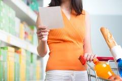 Kobieta przy supermarketem z listą zakupów Obrazy Royalty Free