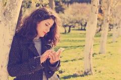 Kobieta przy telefonem z rocznika filtrem Obrazy Stock