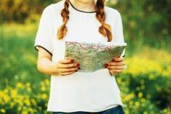 Kobieta przy wsią Młoda caucasian kobieta wycieczkuje z plecakiem patrzeje mapę Zbliżenie kobiet ręki trzyma mapę Fotografia Royalty Free