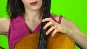 Kobieta przyczepia wiolonczelę z ona palce zielony ekran z bliska zdjęcie wideo