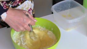 Kobieta przygotowywa ciasto dla torta Miesza składniki w zbiorniku dla robić ciastu zbiory