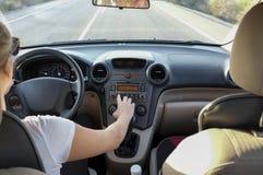 Kobieta przystosowywa radiową tarcza guzika kontrola podczas gdy jedzie obraz royalty free