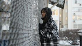 Kobieta przystosowywa szalik sieci ogrodzenie blisko zdjęcie wideo