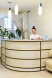 Kobieta recepcjonista w medycznych żakietów stojakach przy recepcyjnym biurkiem obraz royalty free