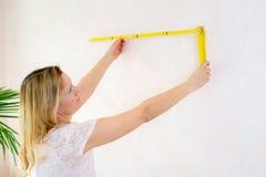 Kobieta redecorate do domu i pracujący z falcowanie miarą obrazy stock