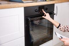 Kobieta regulacyjny kulinarny tryb na piekarnika panelu obraz royalty free