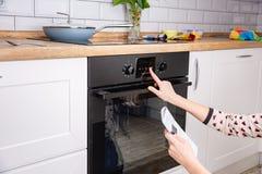 Kobieta regulacyjny kulinarny tryb na piekarnika panelu zdjęcia royalty free