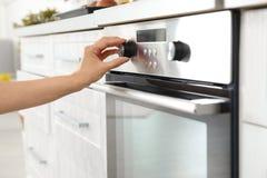 Kobieta regulacyjny kulinarny tryb na piekarnika panelu w kuchni obraz stock