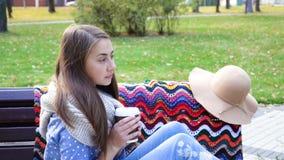 Kobieta Relaksuje na ławce w Pięknym Green Park z filiżanka kawy Wideo ruch atrakcyjna dziewczyna siedzi na drewnianym zbiory wideo