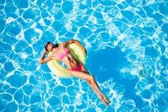 Kobieta relaksuje na gumowym pierścionku w pływackim basenie Fotografia Royalty Free
