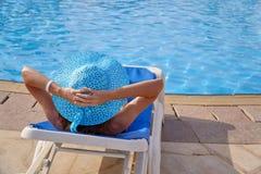 Kobieta relaksuje na leżaku blisko luksusowego lato basenu w hotelu w słomianym kapeluszu, pojęcie czas podróżować zdjęcie stock
