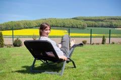 Kobieta relaksuje na słońca lounger z niektóre wzgórzami i rapeseed pole w tle Zdjęcia Royalty Free