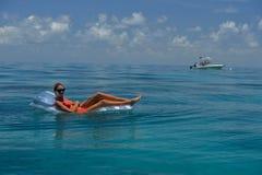 Kobieta relaksuje na spławowym przyrządzie w czerwonym bikini Fotografia Stock