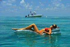 Kobieta relaksuje na spławowym przyrządzie w czerwonym bikini Zdjęcia Royalty Free