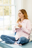Kobieta relaksuje okno z kawą Obraz Stock