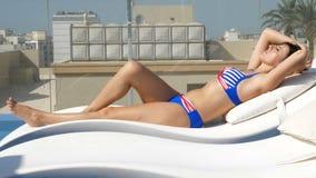 Kobieta relaksuje przy dachu basenem z miasto miastowym widokiem w swimsuit Młodego kobieta modela łgarski puszek przy słońca lou zdjęcie wideo