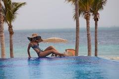 Kobieta relaksuje przy krawędzią nieskończoność basen obraz stock