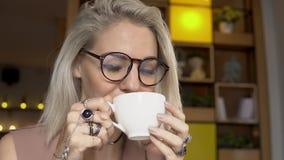 Kobieta relaksuje, uśmiecha się i pije, kawę zbiory