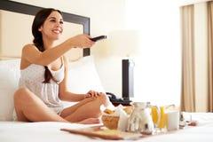 Kobieta relaksuje w łóżkowym mienia pilot do tv zdjęcie royalty free
