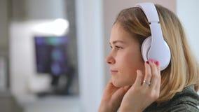 Kobieta relaksuje w domu słuchać dobrą muzykę, odziewa hełmofony zbiory