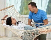 Kobieta relaksuje w hamaka mężczyzna i ono uśmiecha się pozyci Zdjęcia Stock