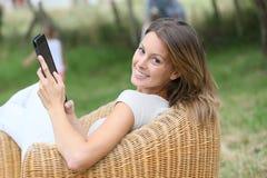 Kobieta relaksuje w karle w ogrodowej używa pastylce zdjęcie royalty free