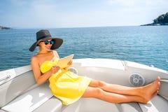 Kobieta relaksuje z cyfrową pastylką na jachcie Zdjęcia Stock