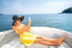 Kobieta relaksuje z cyfrową pastylką na jachcie Zdjęcia Royalty Free