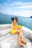 Kobieta relaksuje z cyfrową pastylką na jachcie Zdjęcie Royalty Free