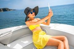 Kobieta relaksuje z cyfrową pastylką na jachcie Obrazy Royalty Free