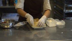 Kobieta robić biali czekolada proszka spadki odsiewa na czekoladowych barach i układają puszek zbiory